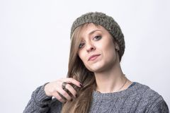 Confident funky hipster girl with knitted gray cap brushing hair looking at camera stock photo