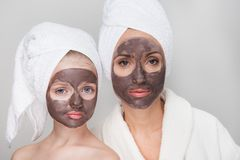 Confident girl and adult woman are using skin care treatment. Portrait of pleasant middle-aged mother in bathrobe and her little daughter are standing together Stock Images