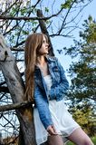 The confident girl with brooding look leaning on the tree stock photos