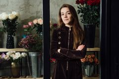 Confident girl business owner of a flower shop stands on a refrigerator background. Royalty Free Stock Photos