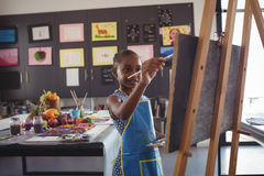 Confident girl painting on canvas. In classroom royalty free stock images