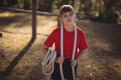 Confident girl standing with rope around her neck. In boot camp stock photography