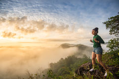 Confident girl standing on top of the mountain. Before sun rise and say yes stock photography