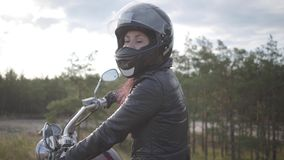 Confident girl wearing black helmet sitting on the motorcycle looking back on the road. Hobby, traveling and active. The girl wearing black helmet sitting on the stock footage