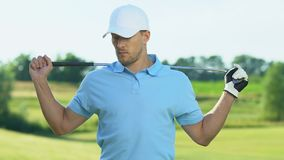 Confident golf player warming-up back and shoulders muscles before hitting ball stock video footage