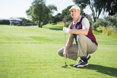 Confident golfer kneeling holding his golf club Stock Image
