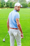 Confident golfer. Rear view of confident golfer holding golf ball and driver while standing on golf course and looking over shoulder Stock Image
