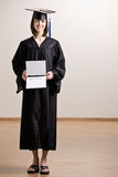 Confident graduating student wearing cap and gown Stock Photo