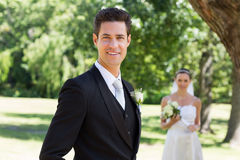 Confident groom with bride in background at garden Royalty Free Stock Photography