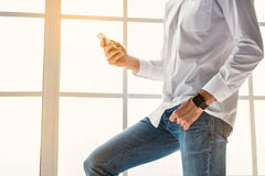 Confident guy messaging on smartphone. Close up of young man using mobile phone. He is standing near window and posing. Smartwatch on his arm Royalty Free Stock Photography