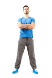 Confident guy posing with crossed hands and head back. Serious confident fit man posing with crossed hands and head back. Full body length isolated over white Stock Images