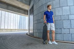 Confident guy with skate on street. Cheerful young man is waiting for someone outdoors. He is standing and holding skateboard. Skater is looking forward with Royalty Free Stock Photos
