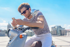 Confident guy using smartphone on bike Stock Photos