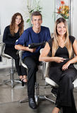 Confident Hairstylists sitting In Salon Royalty Free Stock Image