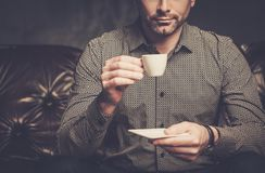 Confident handsome bearded man with cup of coffee sitting on comfortable leather sofa on dark background. royalty free stock photo