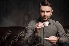 Confident handsome bearded man with cup of coffee sitting on comfortable leather sofa on dark  background. Stock Photos