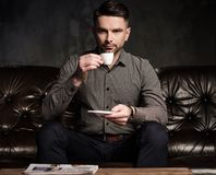 Confident handsome bearded man with cup of coffee sitting on comfortable leather sofa on dark  background. Stock Photo