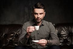 Confident handsome bearded man with cup of coffee sitting on comfortable leather sofa on dark background. royalty free stock photography