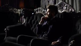 Confident handsome brunette man sitting in luxury interior. Adult successful elegant businessman wearing suit sitting in. Vintage sofa. Entrepreneur in elegant stock video