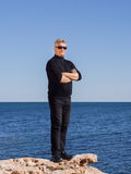 Confident handsome business man standing on a rock. Confident handsome man in a black outfit and sunglasses standing on a rock at the seaside with folded arms Royalty Free Stock Photo