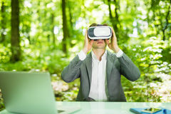 Confident handsome business man with virtual reality glasses pointed with finger at office desk in green park. Business concept. Royalty Free Stock Photography