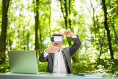 Confident handsome business man with virtual reality glasses pointed with hands at office desk in green park. Business concept. Stock Images