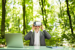 Confident handsome business man with virtual reality glasses pointed with hands at office desk in green park. Business concept. Stock Photo