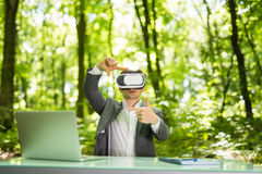 Confident handsome business man with virtual reality glasses pointed with hands at office desk in green park. Business concept. Stock Photos