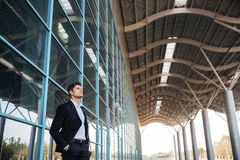 Confident handsome businessman standing with glass building on background Royalty Free Stock Image