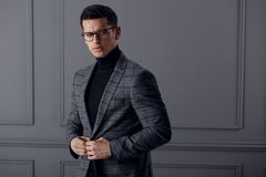 Confident,handsome bussinesman wear stylish gray suit and black eyeglasses and looks with attitude at the camera. stock photos