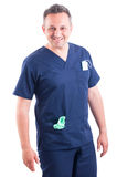 Confident and handsome doctor posing wearing blue scrubs. On white background stock images