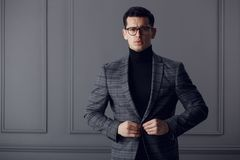 Confident,handsome man of affairs in black eyeglasses, black turtleneck and gray plaid jacket looks serious at camera. stock photos