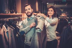 Confident handsome man with beard choosing a jacket in a suit shop. Confident handsome men with beard choosing a jacket in a suit shop royalty free stock photography