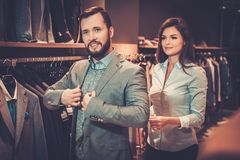 Confident handsome man with beard choosing a jacket in a suit shop. Confident handsome men with beard choosing a jacket in a suit shop royalty free stock images