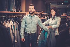 Confident handsome man with beard choosing a jacket in a suit shop. Confident handsome men with beard choosing a jacket in a suit shop stock photography