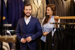 Confident handsome man with beard choosing a jacket in a suit  shop. Stock Photo