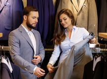 Confident handsome man with beard choosing a jacket in a suit shop. stock photos