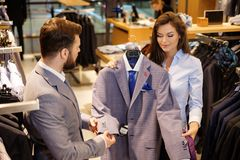 Confident handsome man with beard choosing a jacket in a suit  shop. Royalty Free Stock Photo