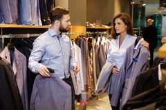 Confident handsome man with beard choosing a jacket in a suit shop. Confident handsome men with beard choosing a jacket in a suit shop stock image