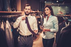 Confident handsome man with beard choosing a tie in a suit  shop. Stock Photo