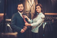 Confident handsome man with beard choosing a tie in a suit  shop. Royalty Free Stock Photography