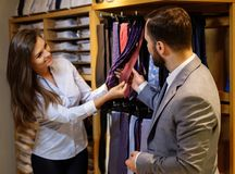 Confident handsome man with beard choosing a tie in a suit  shop. Stock Image