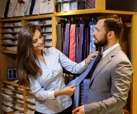 Confident handsome man with beard choosing a tie in a suit  shop. Royalty Free Stock Photo