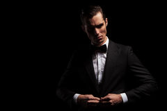 Confident handsome man in black posing in dark studio. Portrait of confident handsome man in black suit with bowtie posing in dark studio background while Royalty Free Stock Photo