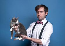 Confident handsome man in shirt, pink bow tie and suspender holding on outstretched arms cute grey cat and looking at camera royalty free stock images