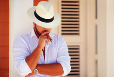 Confident handsome man smoking cigar, while leaning on the wall Stock Photos