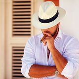 Confident handsome man smoking cigar, while leaning on the wall Royalty Free Stock Photo