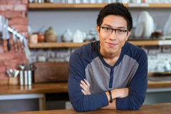 Confident handsome man standing in cafe with arms crossed. Confident handsome smiling asian young man in glasses standing in cafe with arms crossed Stock Photography
