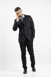 Confident handsome man in suit on the phone walking towards camera looking away Royalty Free Stock Photography