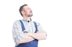 Confident handsome mechanic holding arms crossed and looking up Royalty Free Stock Images